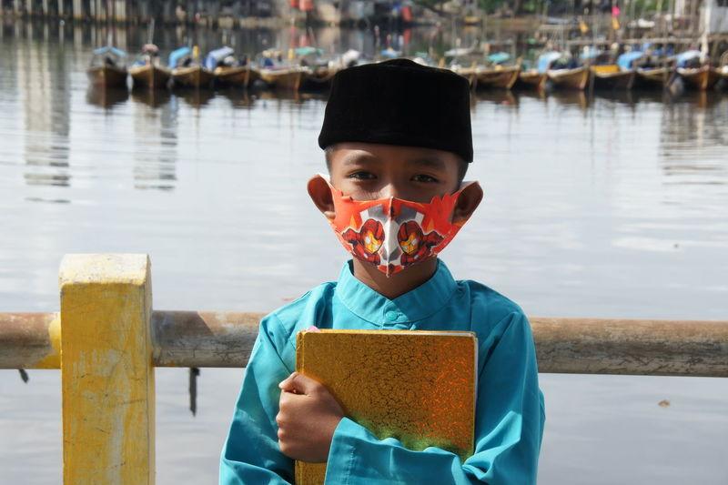 Portrait of boy holding water