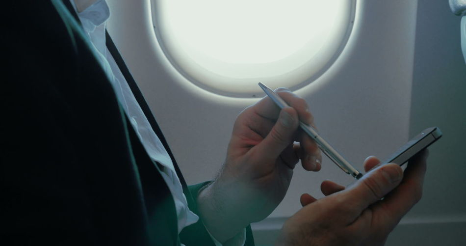 Midsection of person holding mobile phone in airplane