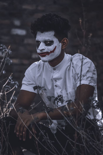 Man with face paint crouching on land