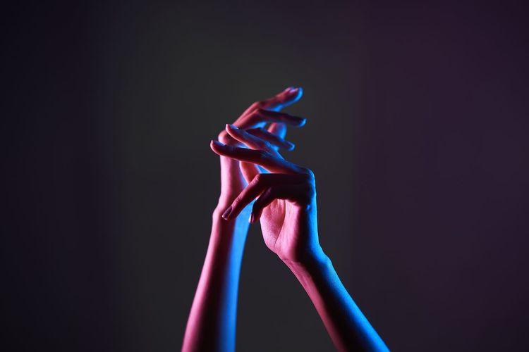 Close-up of hand holding illuminated lighting equipment against black background