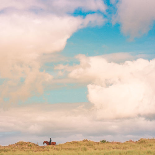 Mid distance of man horseback riding on grassy field against cloudy sky