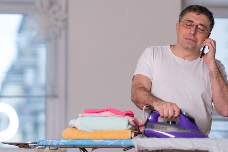 Man Talking On Phone While Ironing Cloth At Home