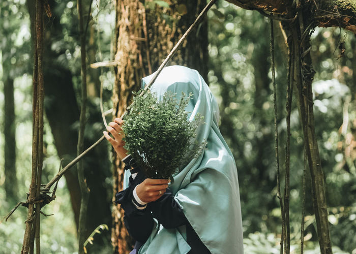 Woman in hijab covering face with plants in forest