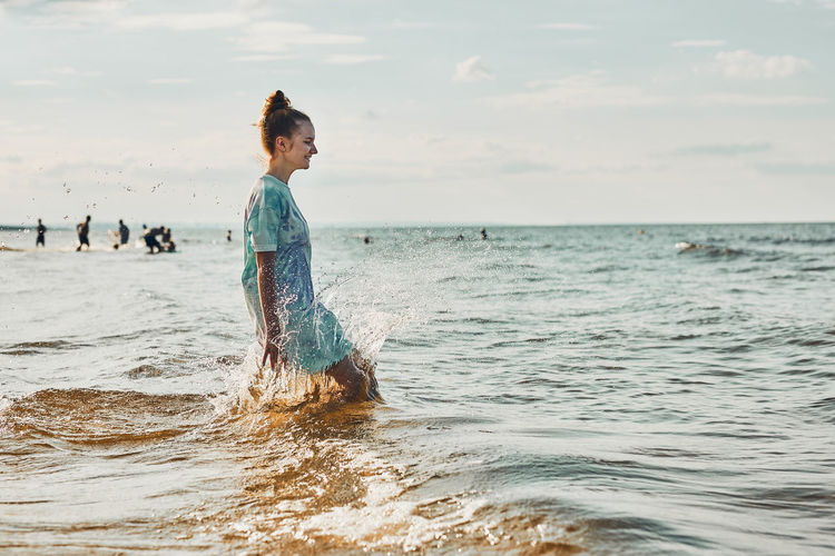 Girl enjoying sea jumping over waves spending a free time over sea on a beach at sunset