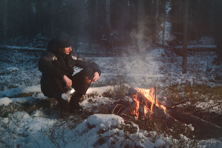 Full length of man sitting by campfire in forest during winter