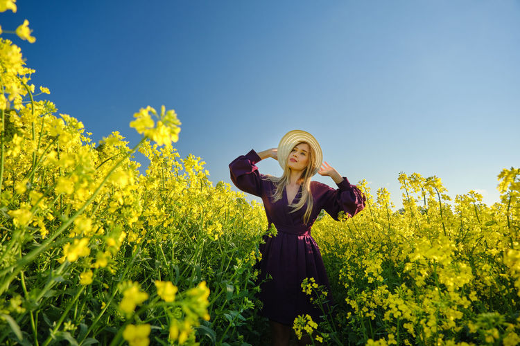 Full length of young woman with yellow flowers on field