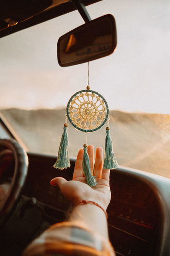 Midsection of man holding dream catcher in car