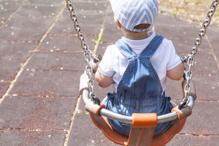 Rear view of boy swinging in swing at playground