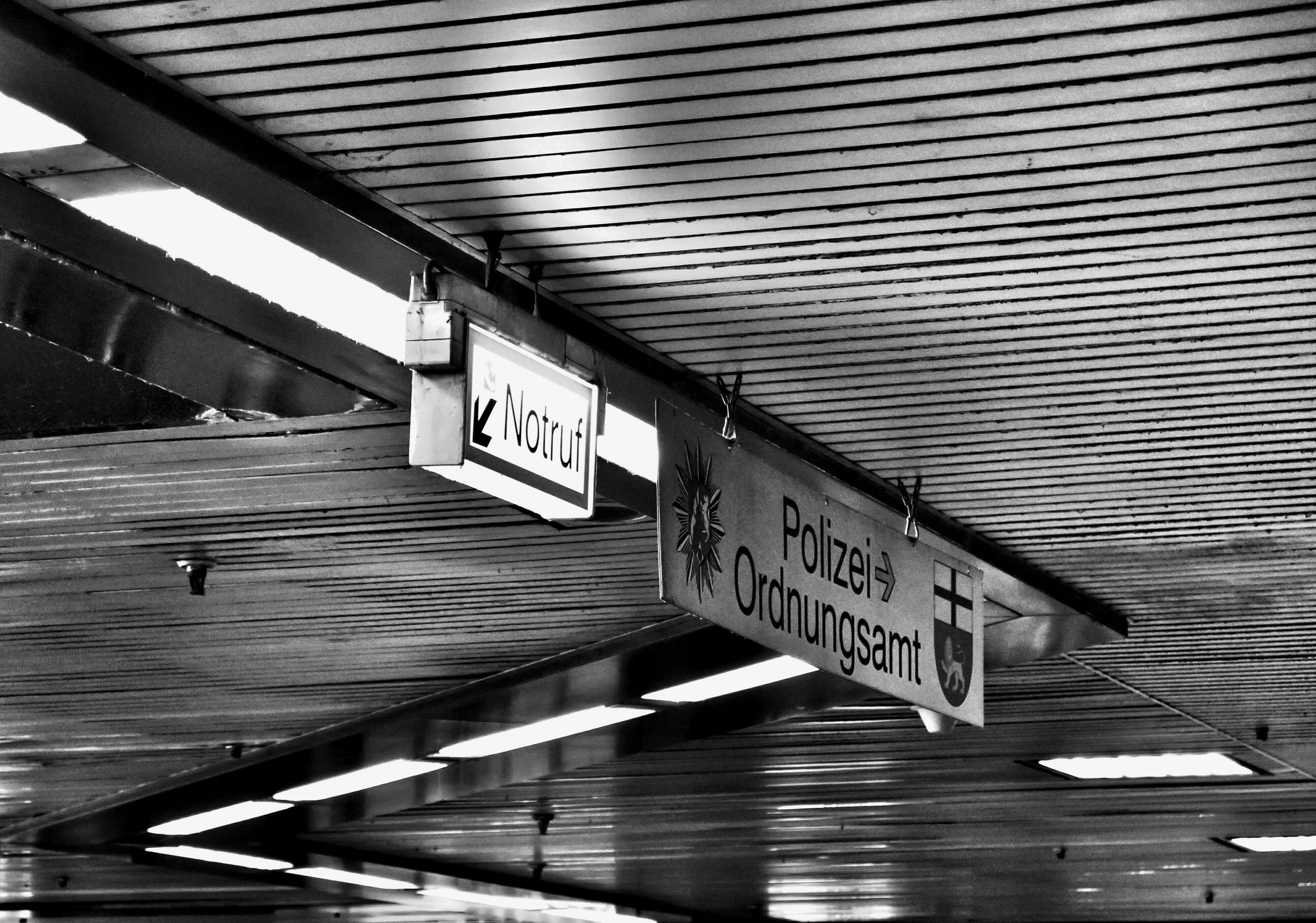 text, built structure, western script, architecture, communication, building exterior, information sign, indoors, low angle view, city, railing, no people, bridge - man made structure, day, sign, reflection, ceiling, modern, railroad station