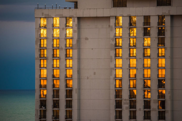 View of building illuminated at waterfront during dusk