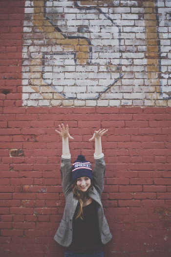 Portrait of cheerful beautiful woman standing with arms raised against brick wall