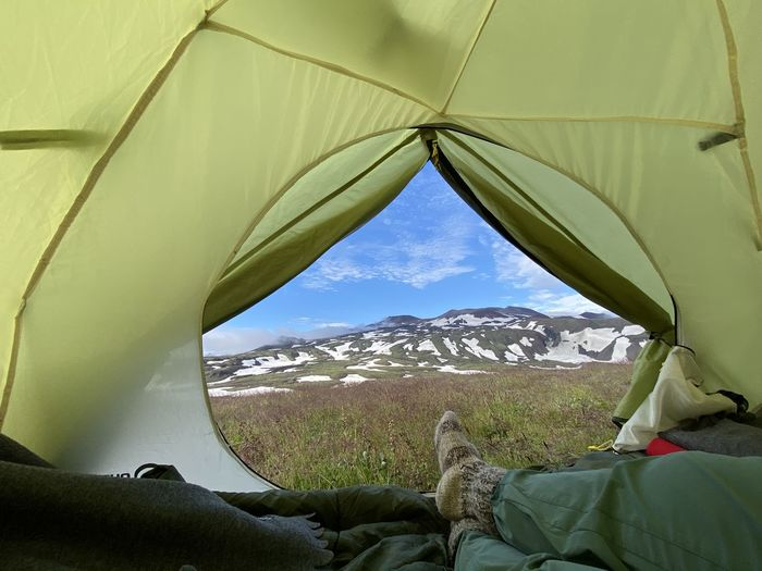 Low section of person relaxing in tent