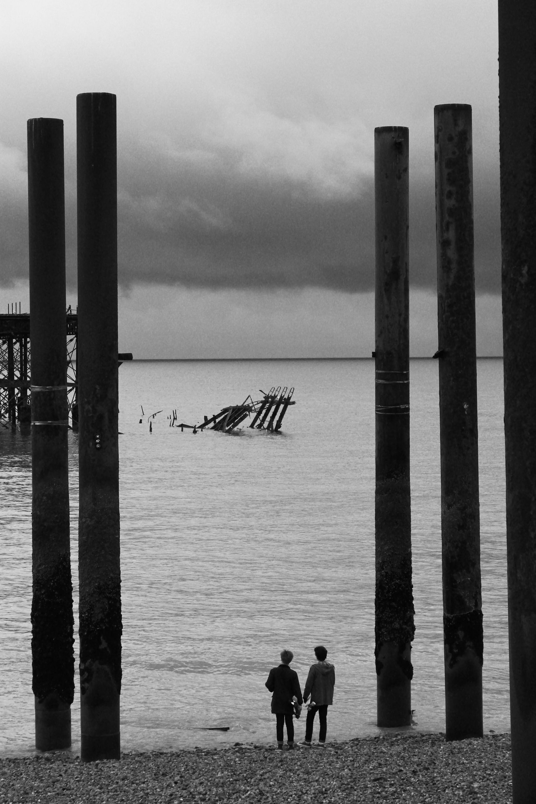 sea, sky, water, horizon over water, beach, men, built structure, cloud - sky, pier, silhouette, lifestyles, shore, person, architecture, leisure activity, standing, nature, wooden post