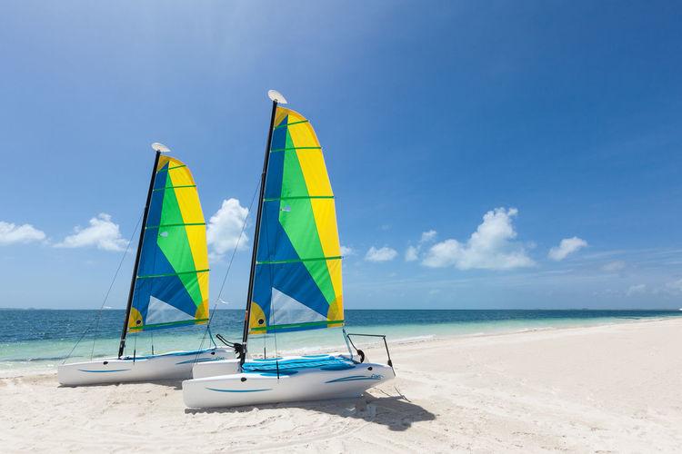 Sailboats on beach against cloudy sky