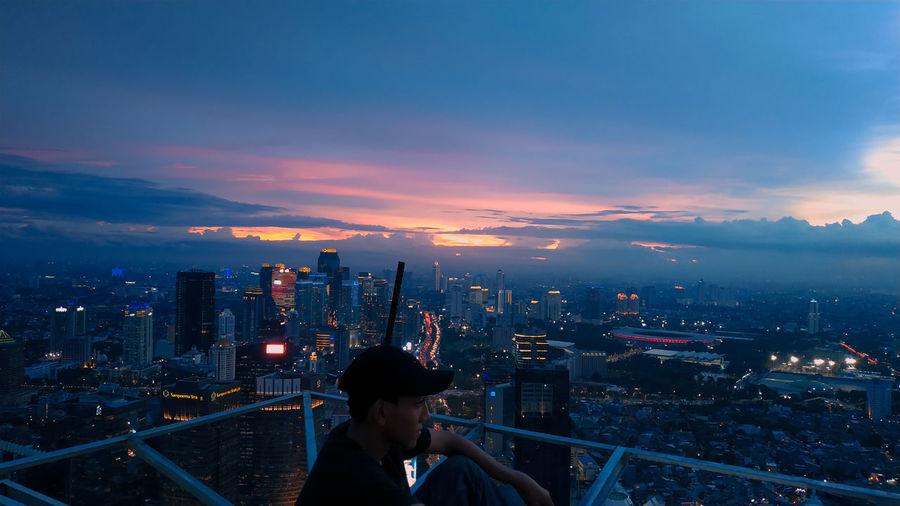 Man in illuminated city at dusk