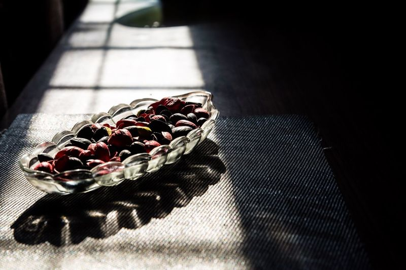 Sunlight falling on nuts in glass bowl at table