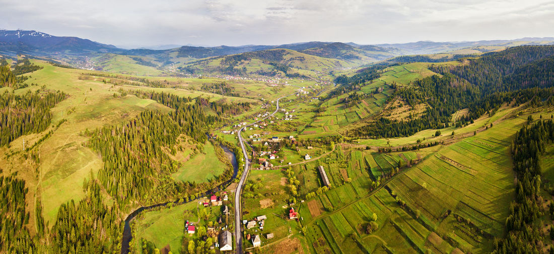 Aerial view of green landscape against sky