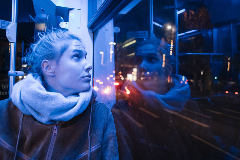 Young woman looking thought window at night
