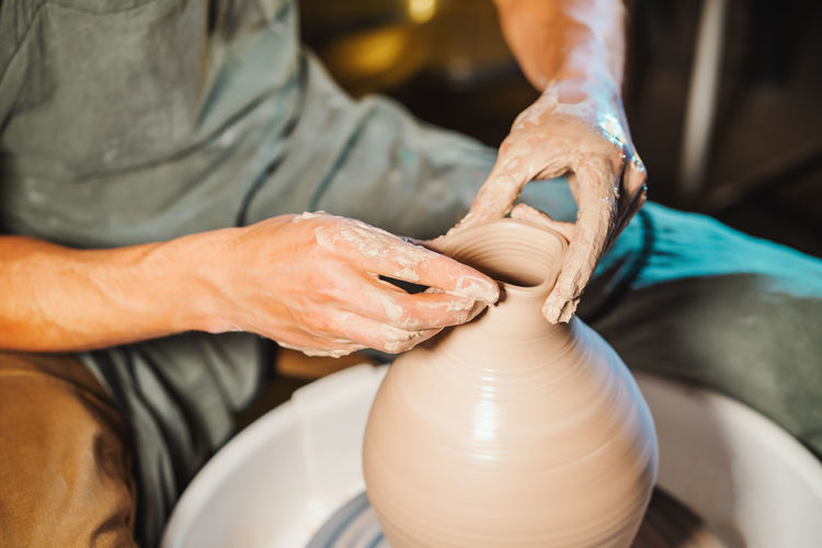 Cropped Hands Of Potter Making Pot In Pottery Workshop