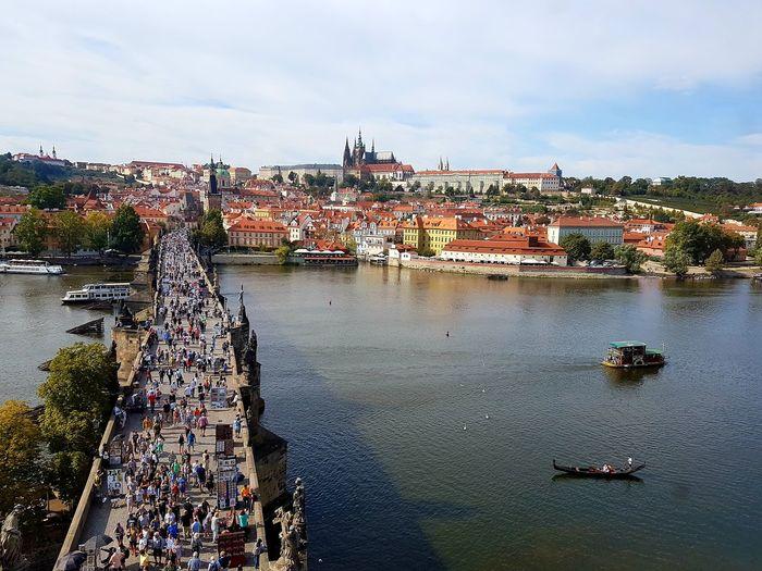 People on footbridge over river in city