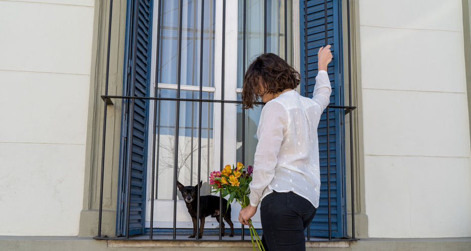 Back view photo of a girl with her dog holding a bouquet of flowers, in front of old iron window