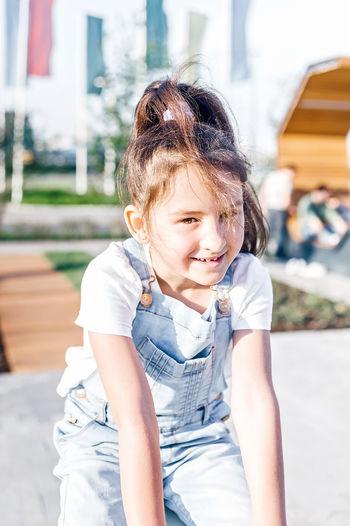 Portrait of smiling girl kneeling on footpath