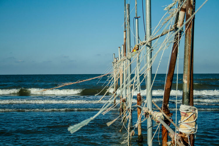 Poles in sea against clear blue sky during sunny day