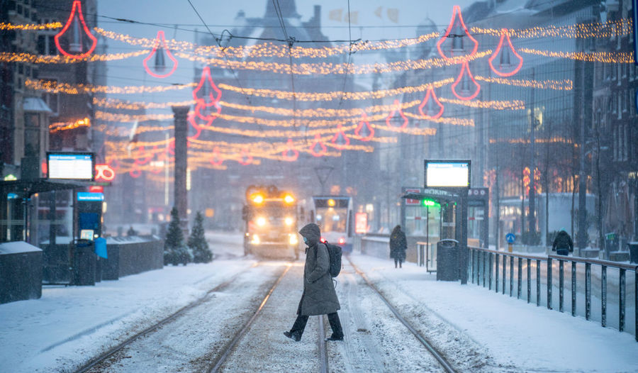 Woman walking on snow covered city street during winter