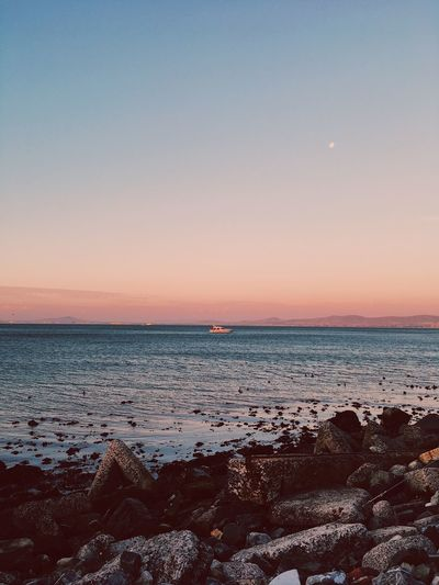 Tranquil scene at dusk, of the ocean. Cape Town. Beauty In Nature Calm Sea Cloudless Sky Dusk Flat Sea Horizon Over Water Moon No People Ocean Pink Hue Sunset Sunset #sun #clouds #skylovers #sky #nature #beautifulinnature #naturalbeauty #photography #landscape Tranquility Water