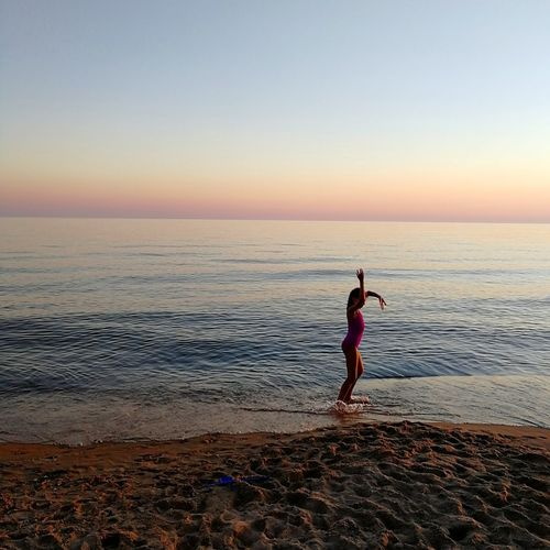 Side view of girl standing at beach against clear sky during sunset
