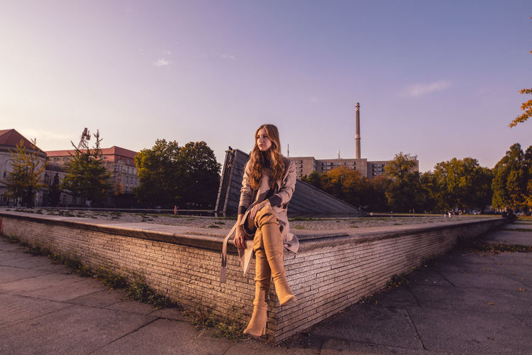 Young woman sitting on retaining wall against sky