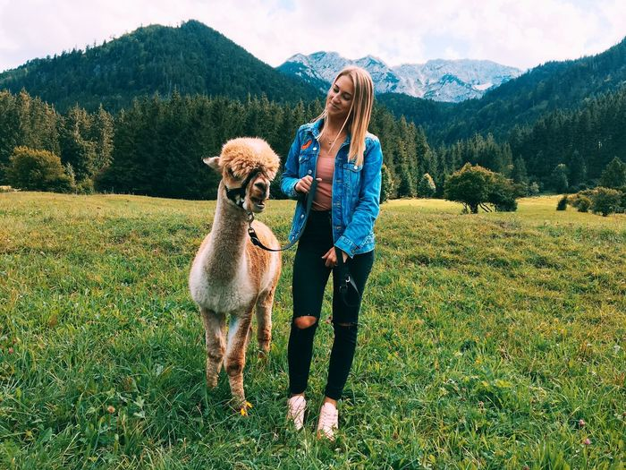 Smiling woman with llama standing on field