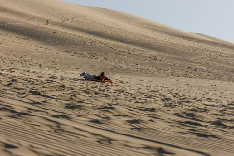 Picture of a young man sandboarding at sunset, Huacachina, Ica, Peru Desert Dunes Extreme Peru Huacachina Ica Outdoors Sand Sand Surfing Speed Sport Sunset