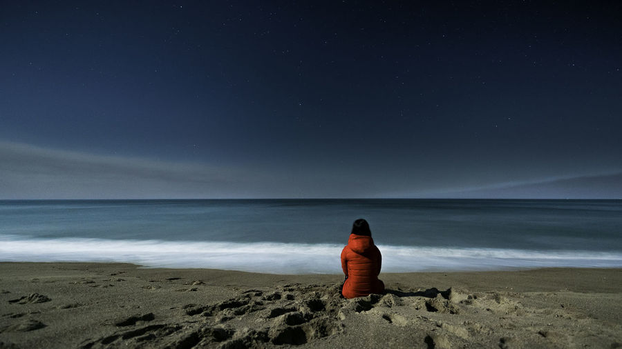 Rear view of woman sitting at beach against sky at night