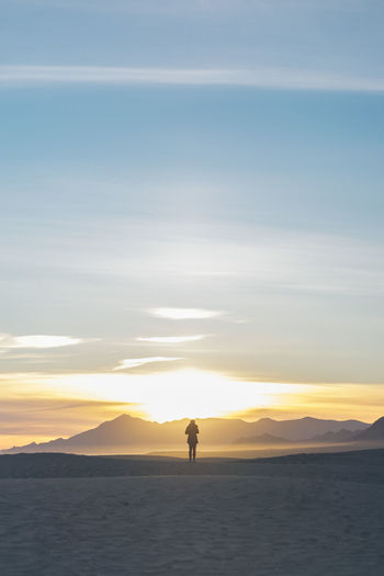 Silhouette man standing on shore against sky during sunset