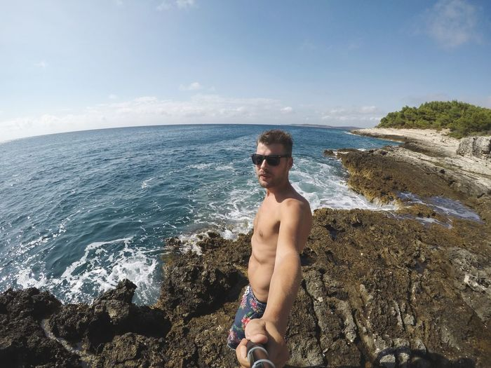 Portrait of shirtless man standing on rocky shore against sky