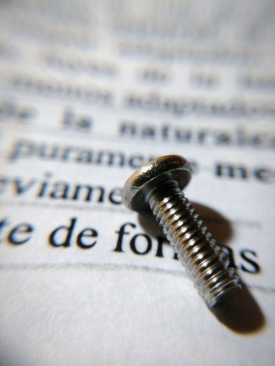 Close-up of screw on paper