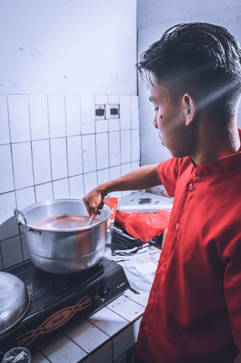 Side view of man preparing food at home