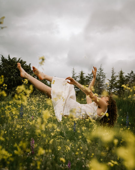 Woman on field by trees against sky
