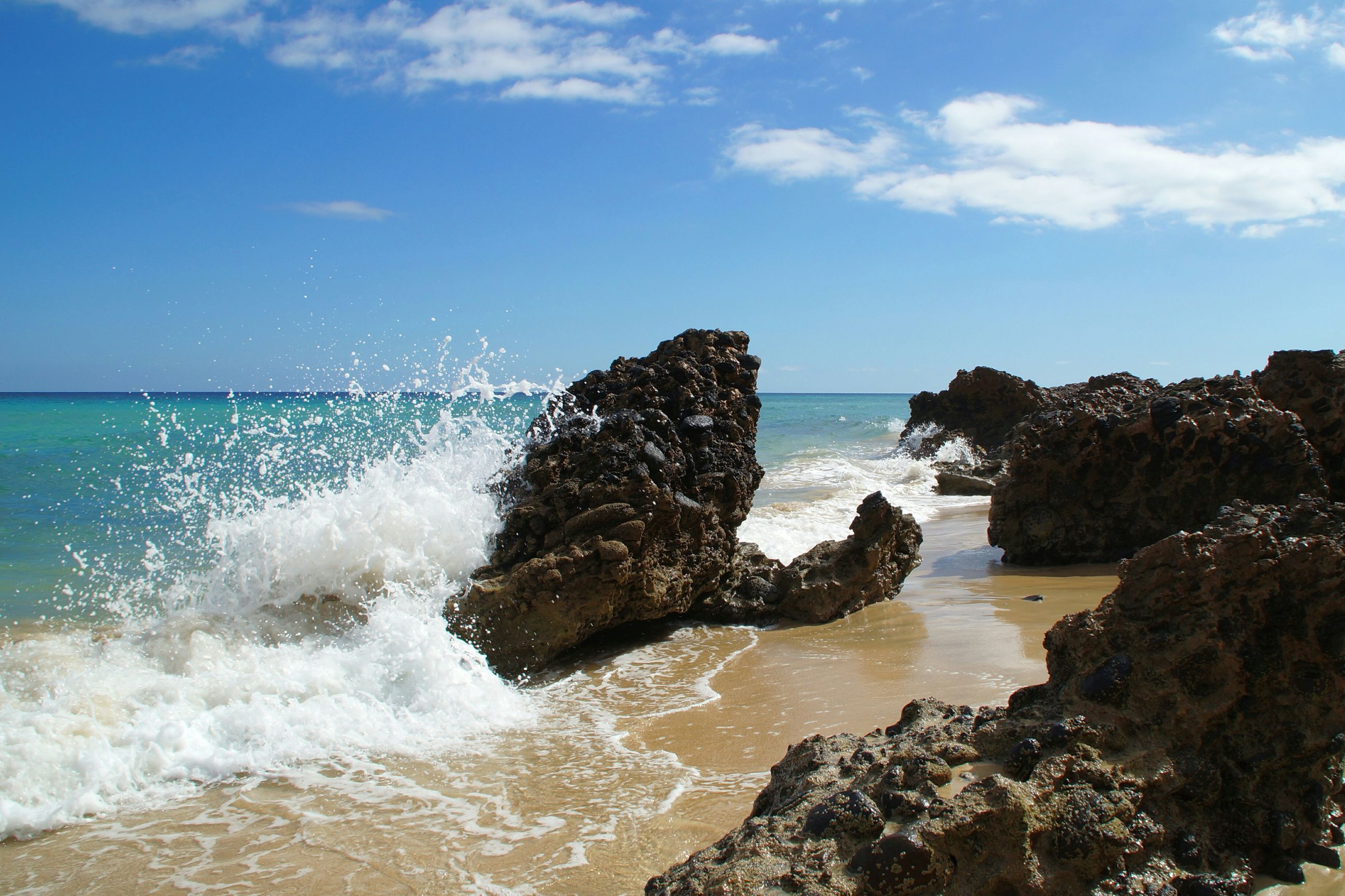 sea, water, horizon over water, sky, beach, scenics, beauty in nature, shore, rock - object, wave, tranquility, tranquil scene, nature, blue, surf, cloud - sky, idyllic, day, splashing, rock formation