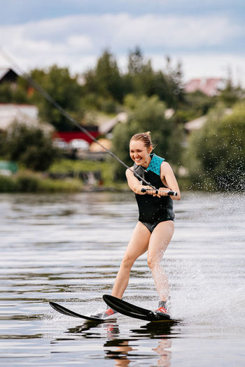 Full length of woman holding umbrella in lake