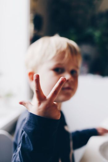 Close-up portrait of cute boy showing peace sign
