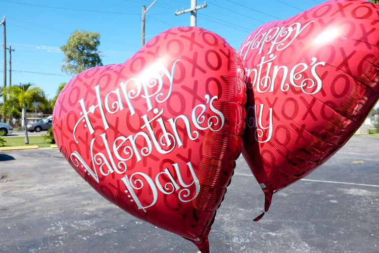 Two red Valentine's Day balloons Happy Valentine's Day Love Valentine's Day  Balloons Close-up Communication Day No People Outdoors Red Road Road Sign Sky Sunlight Text Valentine Balloon