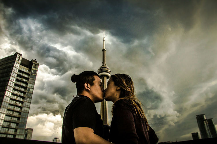 Low Angle View Of Couple Kissing While Standing Against Building In City