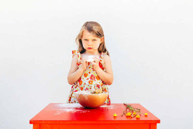 portrait of a little girl with a soiled face flour, isolated on white background, wearing a flower theme dress. A bowl with cookies and yellow flowers are on the table Portrait Kid Girl Soiled Face Flour Isolated White Background Flower Dress Springtime Summer Caucasian Cookie Cookies Baking Food Child Blond Hair Red Table Bowl Cute Biscuits Females Sneaky Sweet Calories Dessert Eat Temptation Childhood Female Cheerful Beauty Little Girl Cooking Sweet Food Indoors  Girls One Person Front View Women Studio Shot Copy Space Holding Lifestyles Wall - Building Feature Food And Drink Innocence Chef Springtime Decadence