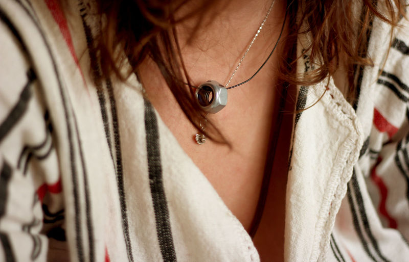 Midsection of woman wearing nut pendant