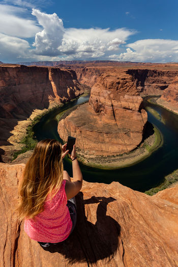 Rear view of woman using phone while sitting on cliff against sky
