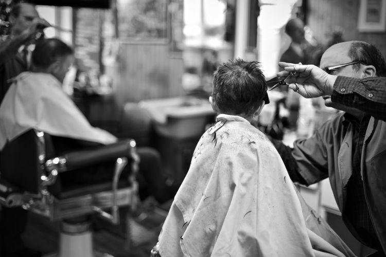 Barber cutting hair of boy
