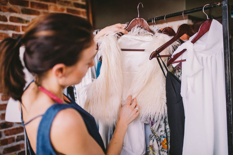 Female Fashion Designer Holding Clothes On Rack At Home