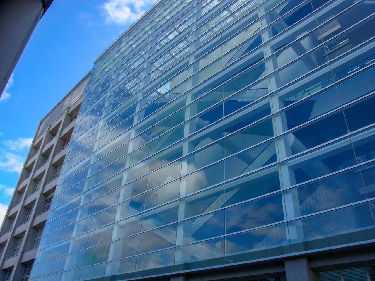 LOW ANGLE VIEW OF MODERN OFFICE BUILDING AGAINST BLUE SKY